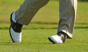 twisting feet of golfer in motion